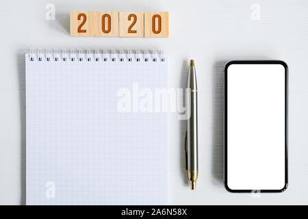Mock up von Smartphone, leeren Blatt Spirale notebook, Metall Kugelschreiber, Holz- Würfel mit Zahlen als Symbol für das neue Jahr 2020 auf weißem Hintergrund. - Stockfoto