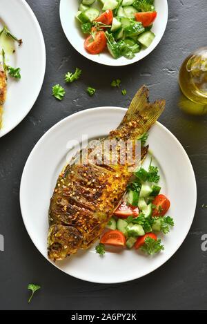 Gebratener Fisch mit gesunden Salat von frischem Gemüse auf dem Teller über schwarzen Stein. Ansicht von oben, flach - Stockfoto