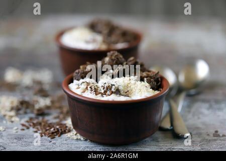 Keto Diät. Griechischer Joghurt mit Leinsamen, Sesam und Schokolade knirscht. Keto freundlich Frühstück oder Dessert. - Stockfoto