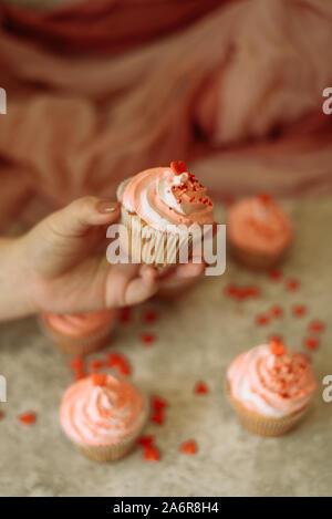 Mädchen, dass eine Cupcake mit rosa Creme auf den Valentinstag. Der Mann gibt eine süße mit dem Valentinstag. - Stockfoto