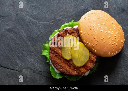 Frisch gegrillten pflanzlichen burger Patty in Brötchen mit Salat, Gurke und Soße auf schwarzem Schiefer isoliert. Ansicht von oben. Kopieren Sie Platz. - Stockfoto