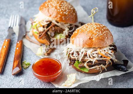 Zog Beef Burger mit Krautsalat und BBQ-Soße auf Papier - Stockfoto