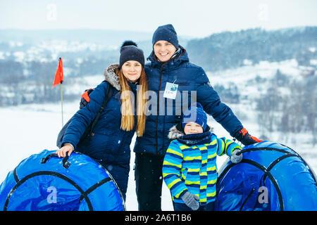 Junge Familie mit Snow tubes posieren. Winter - Stockfoto