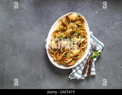 Meeresfrüchte Pasta. Italienische Spaghetti alle Vongole. Venusmuscheln Spaghetti auf weißem Schild mit weißem Wein, grauen Hintergrund. Ansicht von oben - Stockfoto