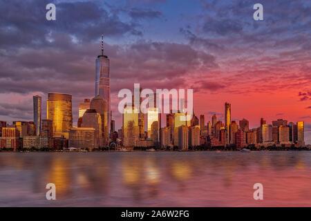 NYC Skyline Sonnenuntergang - die Sonne durch das One World Trade Center, der Freedom Tower in der Skyline von Manhattan in New York City geprägt. - Stockfoto