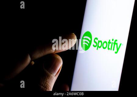 Spotify Logo auf einem Bildschirm des Smartphones in einem dunklen Raum und einen Finger zu berühren. - Stockfoto
