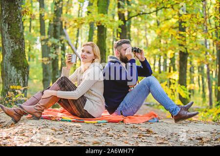 Entspannen Sie im Park zusammen. Glücklich liebend Paar im Park zusammen entspannen. Verliebtes paar Touristen entspannende Picknick Decke. Mann mit Fernglas und Frau mit Metall Becher genießen Sie Natur Park. Park Datum. - Stockfoto