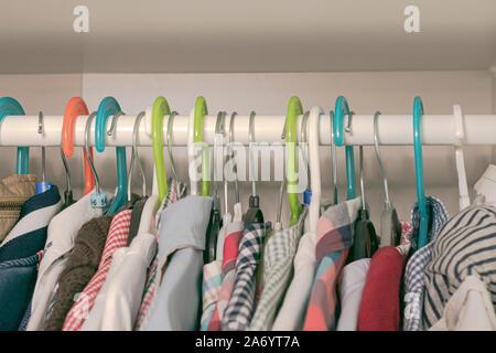 Satz farbiger Aufhängungen und der Kleidung der Kinder hängen auf einem Wäscheständer in einem Schrank - Stockfoto