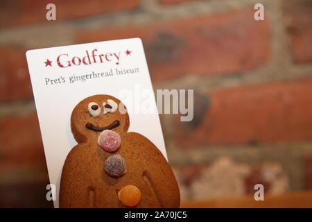 Godfrey, Gingerbread Man Pret's Keks mit einem schlecht iced Auge gegen Ziegel Hintergrund - Stockfoto