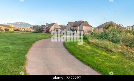 Panorama rahmen Nahaufnahme von einem Weg inmitten thegrasses eines Golfkurses mit weit entfernten Häuser - Stockfoto