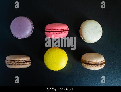 Makronen Cookies auf eine dunkle Leinwand Hintergrund. Blick von oben. - Stockfoto