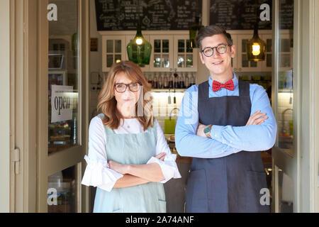 Portraitfotos von Frau mittleren Alters und Jungen Mann zusammen im Cafe Eingang und warten auf ihre Gäste. Kleine Unternehmen. - Stockfoto