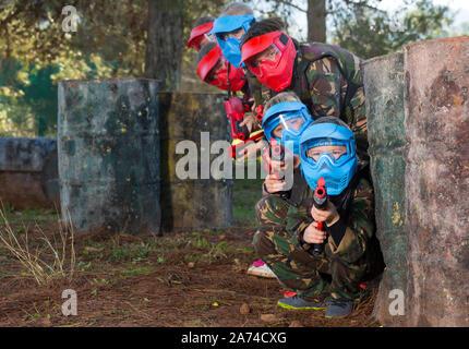 Gruppe von froh Kinder in Datei und Masken spielen paintball zielt mit der Waffe im shootout im Freien - Stockfoto