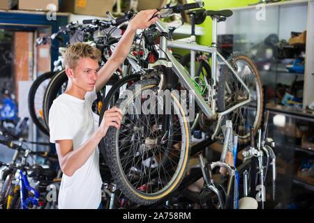 Der Mensch ist die Überprüfung der Reifen am Rad im Store. - Stockfoto