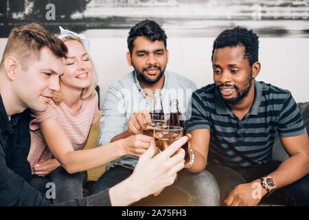 Beste Freunde entspannt zu Hause. Gruppe von fröhlich multikulturellen Freunde in Freizeitkleidung sitzt auf der Couch, Flaschen und Gläser mit Getränken, smili - Stockfoto