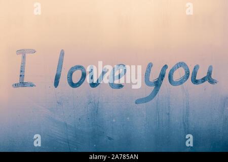 Inschrift auf beschlagene Fenster. Ich liebe Dich. Handschriftlichen text auf nassen Glas. Erklärung der Liebe. Die Worte auf blauem Hintergrund im regnerischen Tag. - Stockfoto