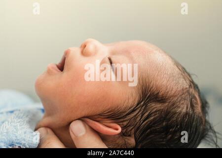 Asiatische neugeborenes Baby Boy ist entspannt und schläfrig nach Badewanne in der ersten Zeit des Lebens. Mutter oder Vater schließen Ohren von Neugeborenen zu schlagen. - Stockfoto