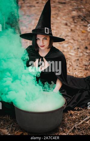 Schwarze Hexe sitzt vor dem Kessel, aus dem grünen Rauch fällt. - Stockfoto