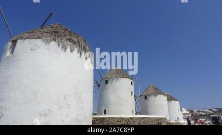 Mykonos, Griechenland: Iconic Windmühlen der Insel Mykonos bei einem Sonnenuntergang nach einem Sommer sonnigen Tag entlang der blauen Meer