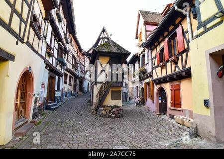 Eguisheim, Frankreich - 24. März 2019: Straße mit Fachwerkhäuser mittelalterlichen Häuser in Eguisheim Dorf an der berühmten Weinstraße im Elsass. - Stockfoto