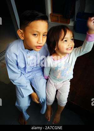 Portrait von asiatischen Bruder und Kleinkind Schwester. Familie Liebe kleben zusammen. Bruder trägt traditionelle malaysische passen. - Stockfoto
