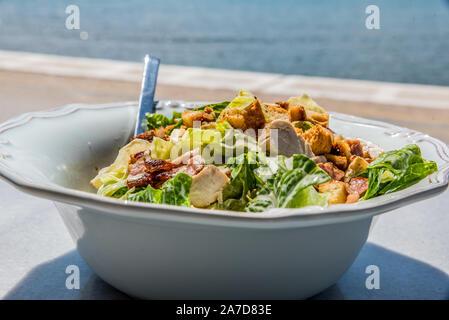 Eine Schüssel von Ceasar Salat auf einem Marmortisch