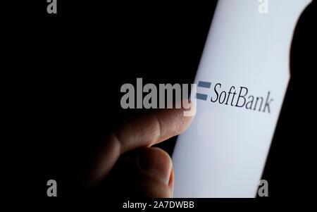 Softbank Logo auf einem Bildschirm des Smartphones in einem dunklen Raum und einen Finger zu berühren. - Stockfoto