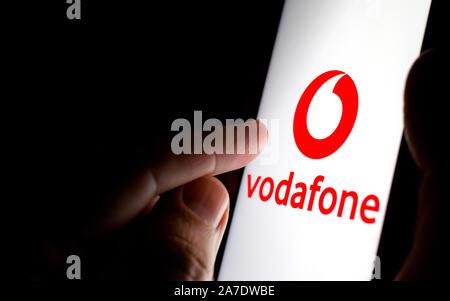 Vodafone Logo auf einem Bildschirm des Smartphones in einem dunklen Raum und einen Finger zu berühren. - Stockfoto