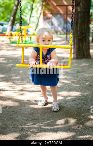 Kinder spielen am Spielplatz im Freien. Kleines Mädchen spielt auf die Schule oder in den Kindergarten Hof. Aktive zicklein auf bunten Schwingen - Stockfoto