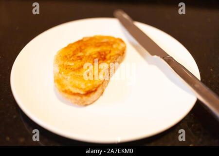 Weiß Sauerteig Toast mit Butter mit silber Messer auf weiße Platte und schwarzem Granit Arbeitsplatte - Stockfoto