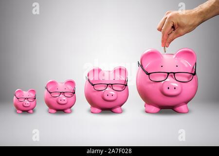 Des Menschen Hand einfügen Die Münze in großen, rosa Sparschwein mit Brillen gegen grauer Hintergrund Stockfoto