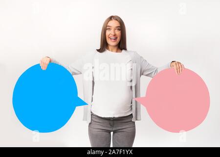 Schwangere Frau mit blauen und rosa Sprechblasen, Studio, Mockup - Stockfoto