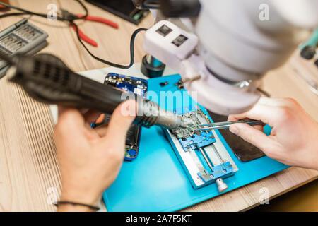 Elektrisches Handwerkzeug und Pinzette in die Hände der Handwerker mit Mikroskop bei der Arbeit - Stockfoto