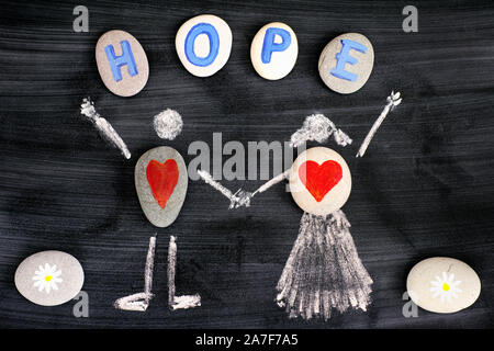 Kiesel mit roten Herzen im Inneren kreidezeichnung von Mann und Frau und Buchstaben Hoffnung auf Kiesel auf der Tafel. Close-up. - Stockfoto