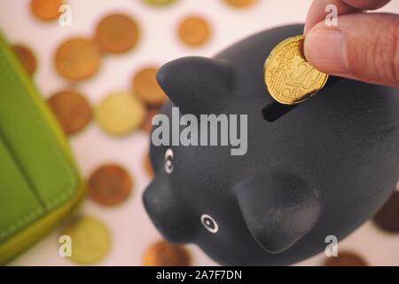 Person, 20 Euro Cent Münze in schwarz Sparschwein. Close Up. - Stockfoto