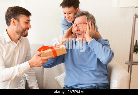 Reifen Sohn und Enkel gratulieren Großvater, Geschenkbox Indoor - Stockfoto