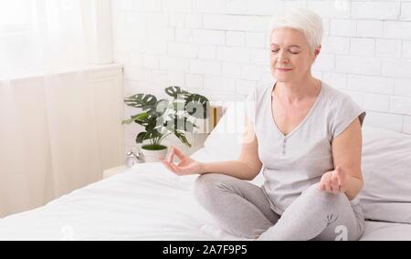 Ältere Frau Yoga, Meditation im Lotussitz auf dem Bett zu Hause. - Stockfoto