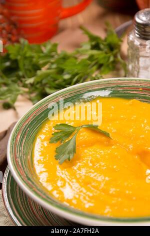 Kürbis creme Suppe in einer Keramikplatte auf dem Küchentisch. Selektiver Fokus - Stockfoto