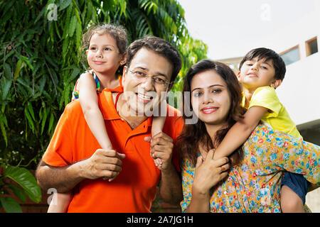 Happy indischer Junge Familie Eltern mit piggyback Fahrt zu den Kindern in - Hof - Ihr Zuhause - Stockfoto