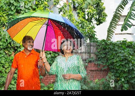 Glücklich Liebende Senior Paar im Regen stehen mit einem Regenschirm Spaß genießen Sie im Park regnerischen Wetter - Stockfoto