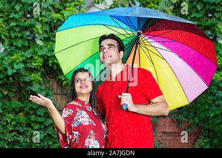 Gerne liebevolle Erwachsene Paare unter dem Dach genießen den Regen an - Park - Stockfoto