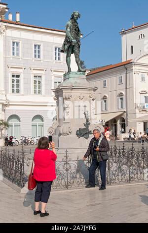 Touristen posieren für ein Foto vor der Statue des Violinisten und Komponisten Giuseppe Tartini, in der Altstadt von Piran, Slowenien. - Stockfoto