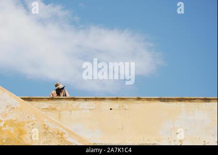 Zurück Blick auf schöne fette Frau mit Hut auf historische Gebäude Terrasse in Gallipoli. Apulien, Italien. Travel Concept. - Stockfoto