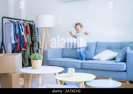 Schöne Kleinkind Kind Mädchen springen auf dem Sofa - Stockfoto