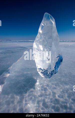 Ein Stück von glitzernden Eis steht auf gefrorenen Baikalsee vor blauem Himmel. Ein langer Riss im Eis. Vertikale Ausrichtung. - Stockfoto