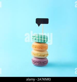 Kreatives Konzept noch leben Ernährung Gesundheit Foto von macarons Amaretti Gebäck Mandeln süß Süßwaren mit Meldung cloud Benachrichtigung auf Blau bac - Stockfoto