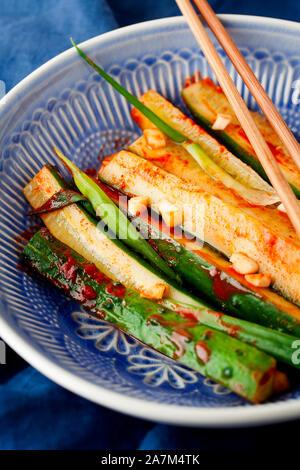 Koreanisches Kimchi Gurke Gurke. marinierten Gurken mit Chili, Knoblauch, grünen Zwiebel in blauen Platte close-up. Gesunden veganen Snack mit probiotischen - Stockfoto