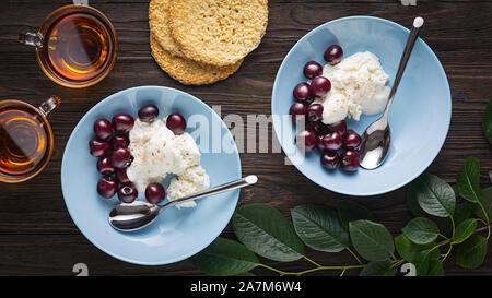Gesundes Frühstück. Quark mit Sauerrahm und reife Kirschen in blau Schalen auf einem Holztisch. Ansicht von oben. - Stockfoto