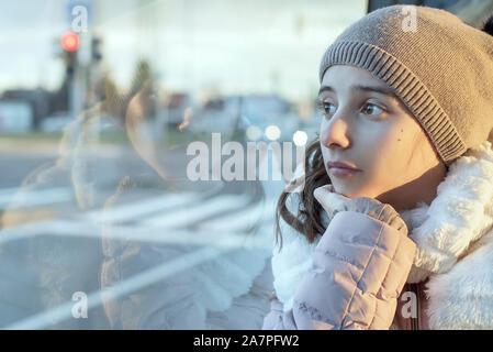 Mädchen Jugendlicher sitzt im Bus und schaut aus dem Fenster, jugendliche Mädchen im Bus freuen Denken sitzt. - Stockfoto