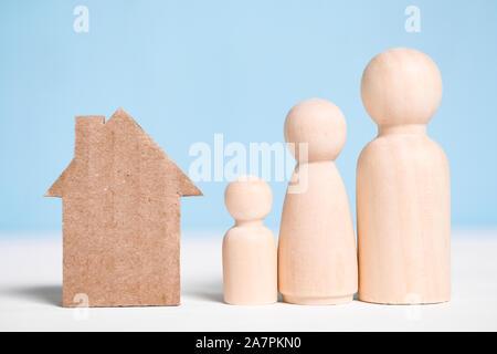 Holzfiguren Familie mit Karton ausschnitt Haus auf blauem Hintergrund. Konzept der Umzug zum neuen Haus, Siedlung, Miete, Hypotheken, Vertreibung. - Stockfoto